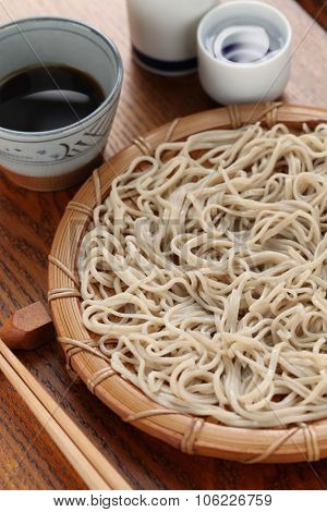 cold soba noodles served on bamboo tray with sake, japanese food