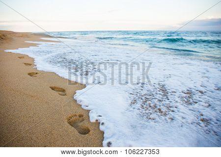 Footprints On Sandy Beach And Sea Wave
