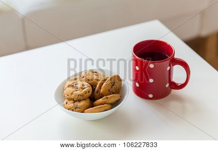christmas, holidays, winter, celebration and still life concept - close up of oat cookies and red tea cup on table at home