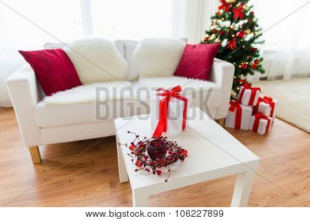 christmas, holidays, celebration and still life concept - close up of gift box, wreath and lantern on table at home