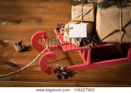 holidays, presents, new year and celebration concept - close up of gift boxes with blank note on red wooden sleigh and pinecones