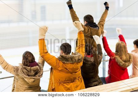 people, friendship, sport and leisure concept - happy friends watching hockey game or figure skating performance on ice rink arena