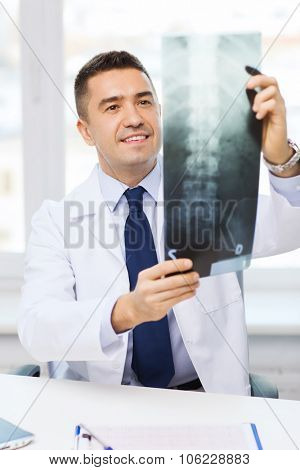 healthcare, rontgen, people and medicine concept - smiling male doctor in white coat looking at x-ray in medical office