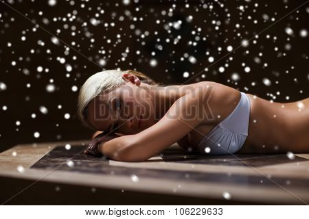 people, beauty, spa, healthy lifestyle and relaxation concept - beautiful young woman lying on hammam table in turkish bath with snow effect