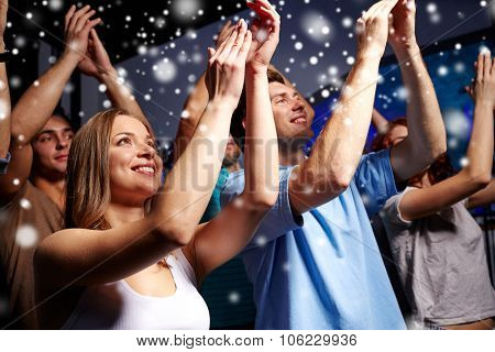party, holidays, celebration, nightlife and people concept - smiling friends applauding at concert in club and snow effect