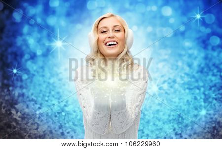 winter, magic, christmas and people concept - smiling young woman in earmuffs and sweater holding fairy dust on her palms over blue glitter or lights background