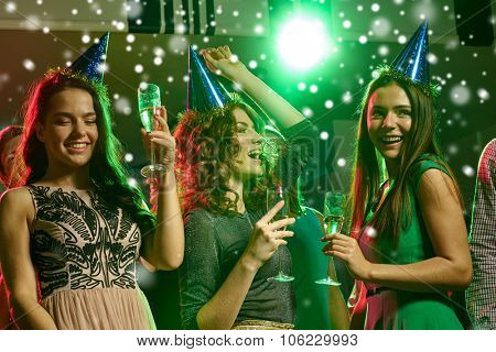 new year party, holidays, celebration, nightlife and people concept - smiling friends with glasses of non-alcoholic champagne in club and snow effect