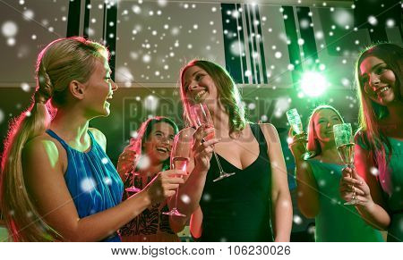 new year party, holidays, celebration, nightlife and people concept - happy young women with glasses of non-alcoholic champagne dancing in club and snow effect