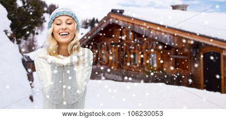 winter, advertisement, vacation, christmas and people concept - smiling young woman in hat and sweater holding something on her empty palms over wooden country house and snowflakes background