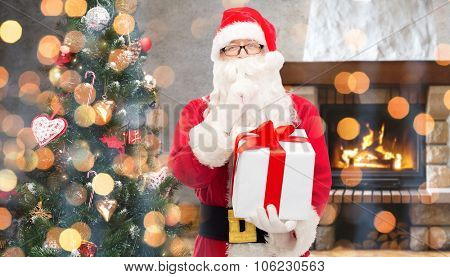 christmas, winter, holidays and people concept - man in costume of santa claus with gift box and tree making hush gesture over home fireplace and lights background