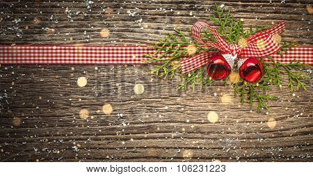 Ribbon bow with jingle bell and fir branch on wood
