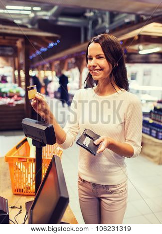 sale, shopping, consumerism and people concept - happy young woman with credit card and wallet buying food at checkout in market