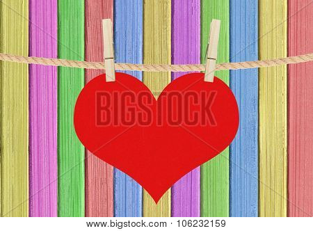Red Heart Hang On Clothespins Over Color Painted Wooden Background