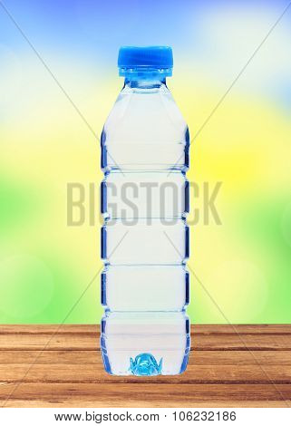 Blue Bottle With Water On Wooden Table Over Blurred Nature Background