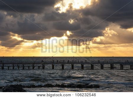 Pier and sea with waves at sunset sky