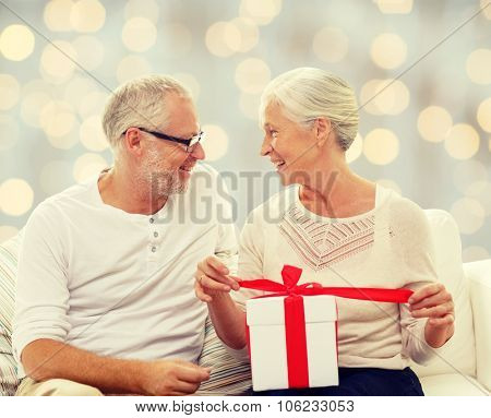 family, holidays, christmas, age and people concept - happy senior couple with gift box over holidays lights background