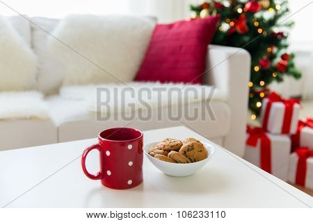 christmas, holidays, winter, celebration and still life concept - close up of oat cookies and red cup on table at home