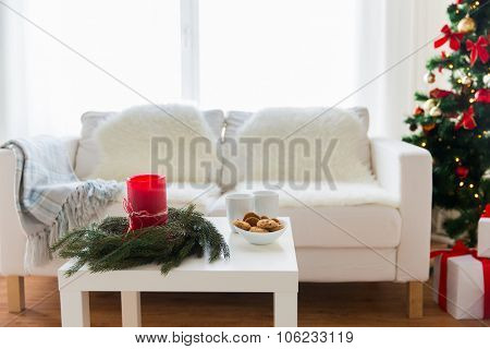 holidays, winter, celebration and still life concept - sofa, table and christmas tree with gifts at home