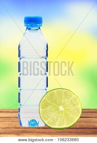 Blue Bottle With Water And Fresh Lime On Wooden Table Over Blurred Nature Background