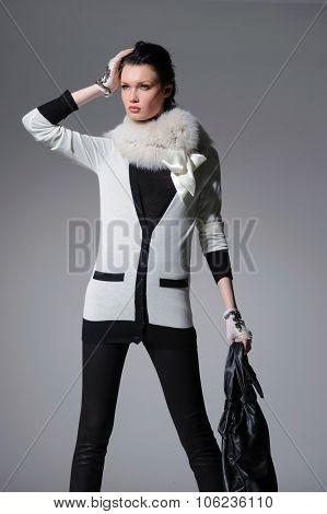 fashion model clothes holding handbag posing-gray background