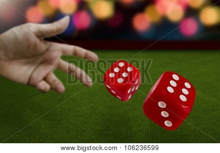 Male hand throwing dice on green felt
