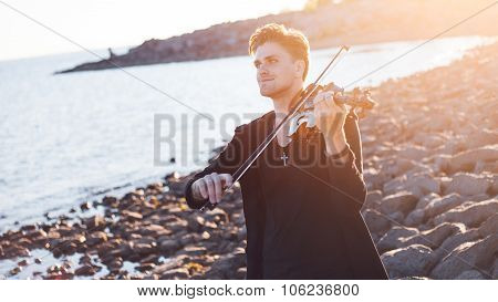 Violinist playing a violin,  young man plays on the background of  sea