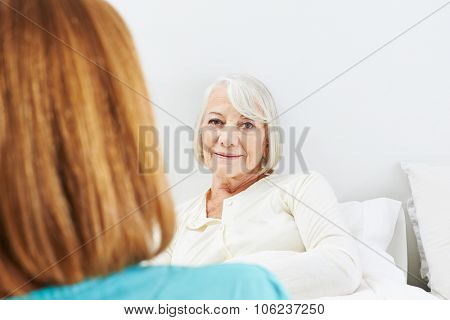Caregiver talking to bedridden senior woman in her bed