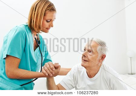 Nurse in nursing home helping senior man getting up from bed