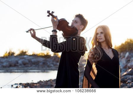 violinist and his Muse,   young man plays on the background of  sea