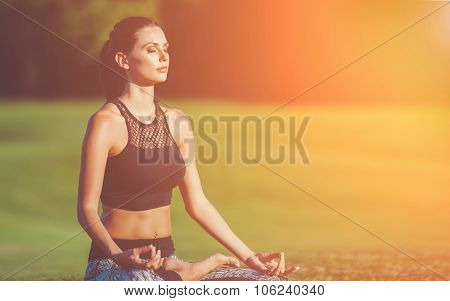 Attractive young woman in a lotus position in green park at sunset