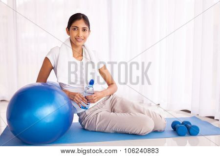 portrait of indian woman sitting on mat with exercise ball