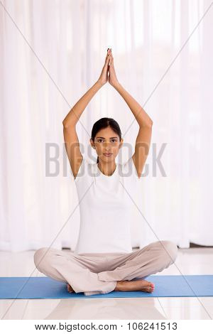 peaceful indian woman yoga meditating at home