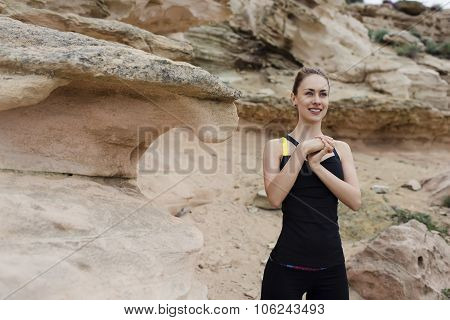 Young female runner doing wrist exercise copy space area for text message