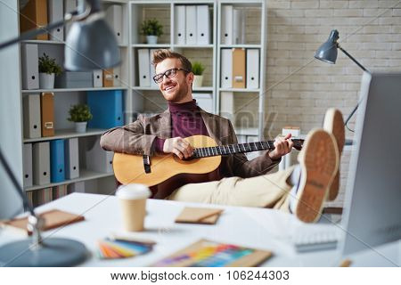 Handsome businessman with guitar singing in office