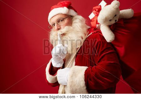 Happy Santa carrying gifts in big red sack