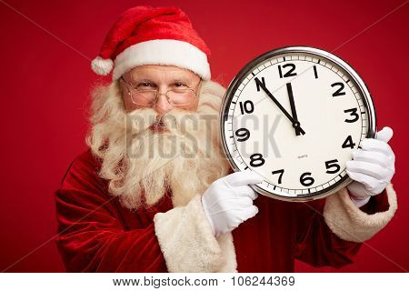 Happy Santa showing at clock showing five minutes to Christmas night