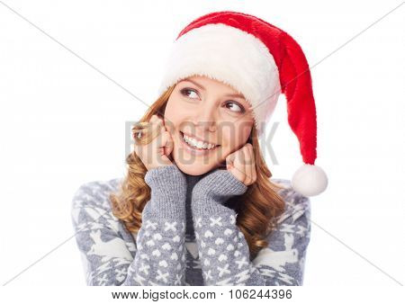 Happy girl in Santa cap looking sideways