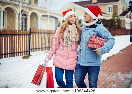 Young couple in Santa caps with giftboxes walking home on Christmas eve after shopping