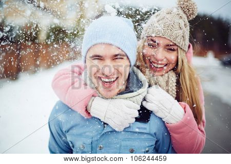Young guy and girl in winterwear enjoying snowfall