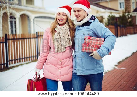 Young couple in Santa caps carrying giftboxes while moving outdoors on Christmas eve