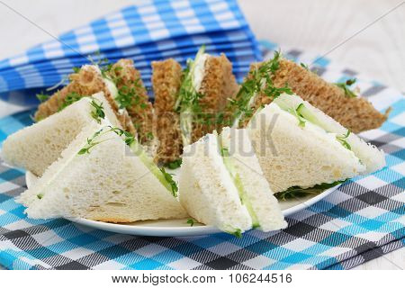 Traditional white and brown cream cheese and cucumber sandwiches and checkered napkins