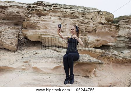 Portrait of young fit woman making self portrait showing super sign for smart phone camera
