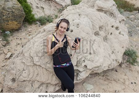 Female jogger taking break while listen to music in heaphones