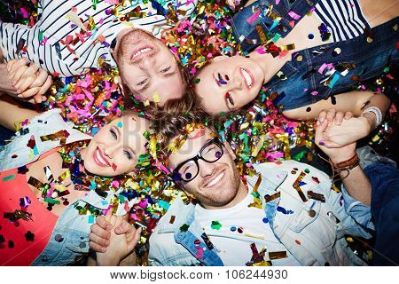 Cheerful friends lying on the floor covered with confetti in the night club