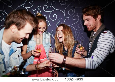 Cheerful friends with flutes of champagne spending time in nightclub