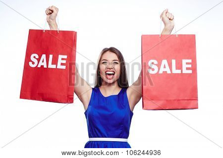 Ecstatic shopaholic holding two paperbags in raised hands
