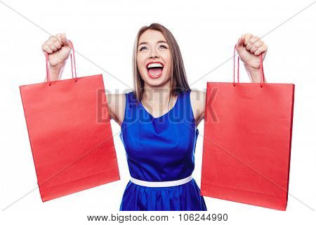 Ecstatic shopaholic with red paperbags in raised hands expressing triumph