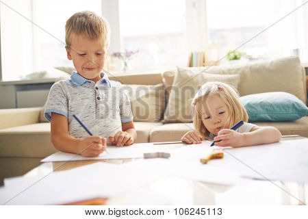 Adorable siblings drawing together at home