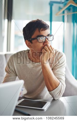 Pensive guy in eyeglasses looking sideways