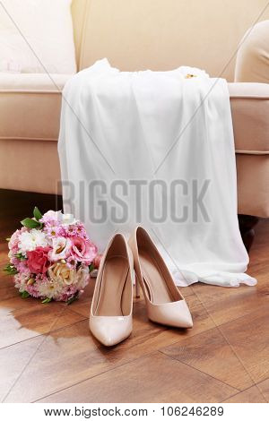Wedding bouquet, bridesmaid dress and shoes in room